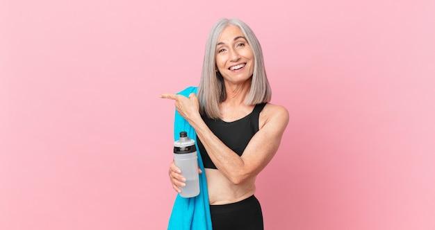 Mulher de meia-idade de cabelo branco parecendo animada e surpresa, apontando para o lado com uma toalha e uma garrafa de água. conceito de fitness