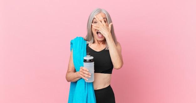 Mulher de meia-idade de cabelo branco parecendo chocada, assustada ou apavorada, cobrindo o rosto com a mão com uma toalha e uma garrafa de água. conceito de fitness