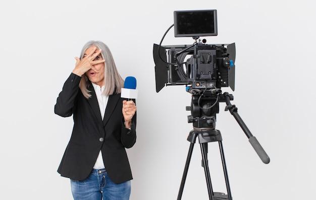 Mulher de meia-idade de cabelo branco parecendo chocada, assustada ou apavorada, cobrindo o rosto com a mão e segurando um microfone. conceito de apresentador de televisão