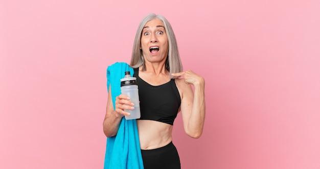 Mulher de meia-idade de cabelo branco parecendo chocada e surpresa com a boca aberta, apontando para si mesma com uma toalha e uma garrafa de água. conceito de fitness