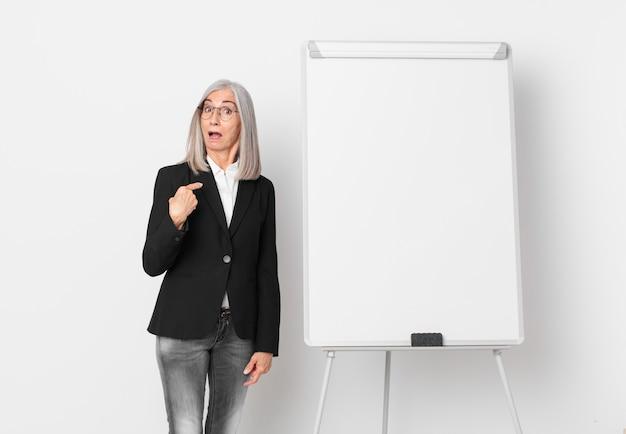 Mulher de meia-idade de cabelo branco parecendo chocada e surpresa com a boca aberta, apontando para si mesma e um espaço de cópia da placa. conceito de negócios