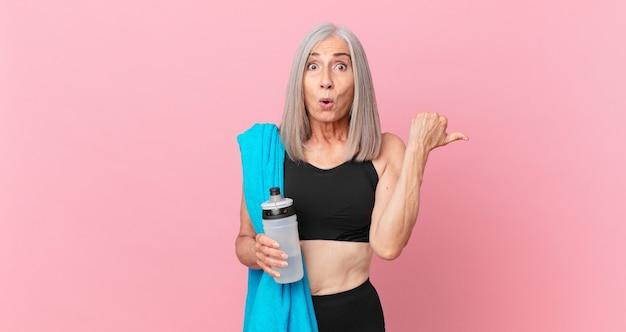 Mulher de meia-idade de cabelo branco parecendo espantada com a descrença com uma toalha e uma garrafa de água. conceito de fitness