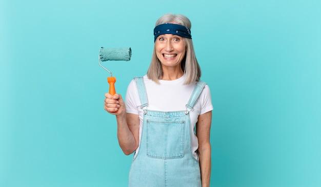Mulher de meia-idade de cabelo branco parecendo feliz e agradavelmente surpresa com um rolo pintando uma parede