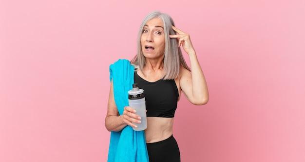 Mulher de meia-idade de cabelo branco parecendo feliz, espantada e surpresa com uma toalha e uma garrafa de água. conceito de fitness