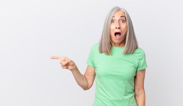Mulher de meia-idade de cabelo branco parecendo muito chocada ou surpresa e apontando para o lado