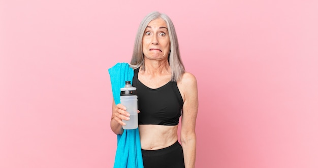 Mulher de meia-idade de cabelo branco parecendo perplexa e confusa com uma toalha e uma garrafa de água. conceito de fitness