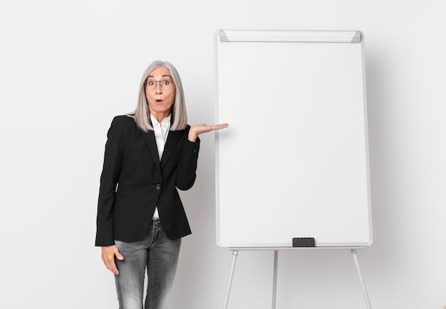 Mulher de meia-idade de cabelo branco parecendo surpresa e chocada, com o queixo caído segurando um objeto e um espaço de cópia da placa. conceito de negócios