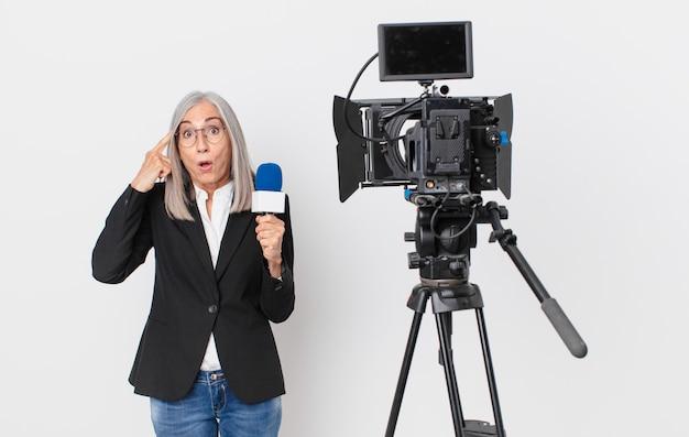Mulher de meia-idade de cabelo branco parecendo surpresa, percebendo um novo pensamento, ideia ou conceito e segurando um microfone. conceito de apresentador de televisão