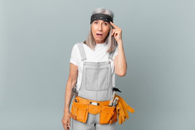 Mulher de meia-idade de cabelo branco parecendo surpresa, percebendo um novo pensamento, ideia ou conceito e usando roupas de trabalho e ferramentas. conceito de limpeza