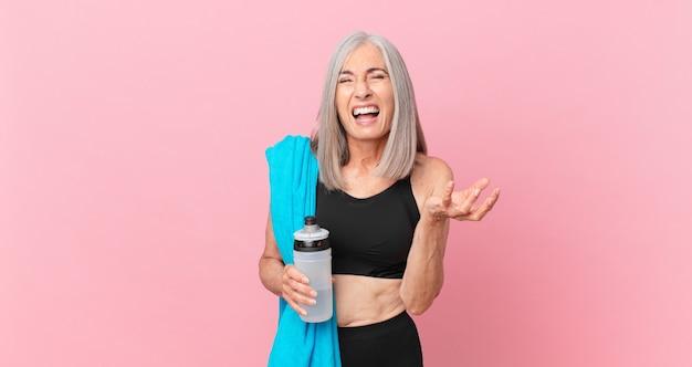 Mulher de meia-idade de cabelo branco parecendo zangada, irritada e frustrada com uma toalha e uma garrafa de água. conceito de fitness