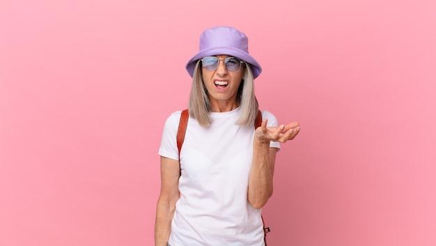 Mulher de meia-idade de cabelo branco parecendo zangada, irritada e frustrada. conceito de verão