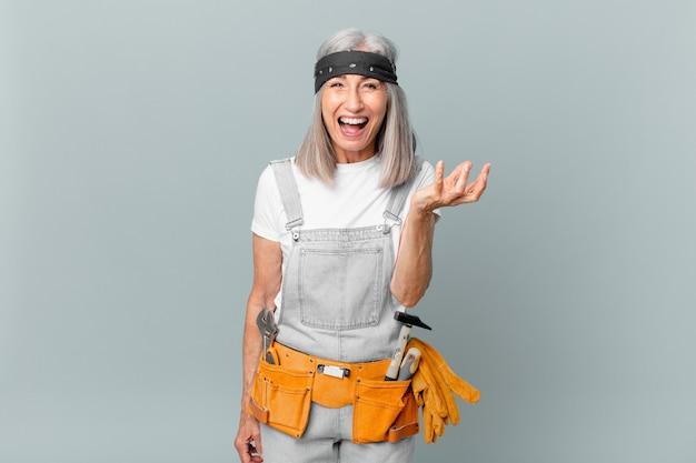 Mulher de meia-idade de cabelo branco parecendo zangada, irritada e frustrada e usando roupas de trabalho e ferramentas. conceito de limpeza