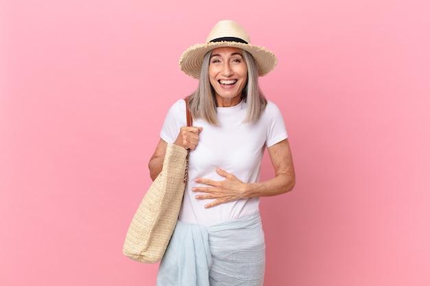 Mulher de meia-idade de cabelo branco rindo alto de uma piada hilária