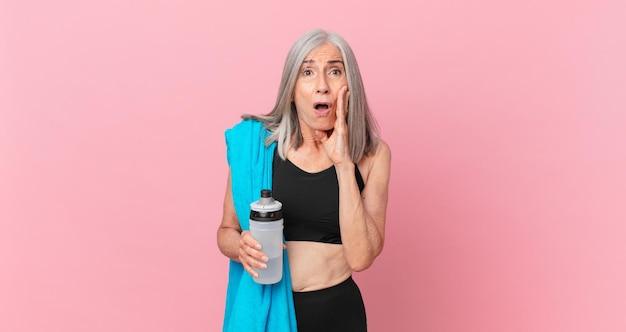 Mulher de meia-idade de cabelo branco se sentindo chocada e assustada com uma toalha e uma garrafa de água. conceito de fitness