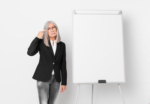 Mulher de meia-idade de cabelo branco se sentindo confusa e intrigada, mostrando que você é louco e um espaço de cópia de placa. conceito de negócios