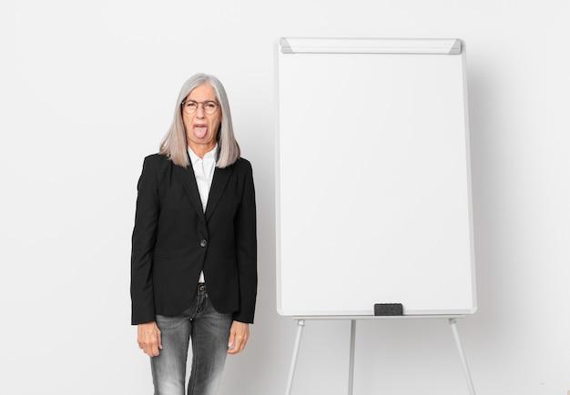 Mulher de meia-idade de cabelo branco se sentindo enojada e irritada e com a língua de fora e um espaço de cópia da placa. conceito de negócios