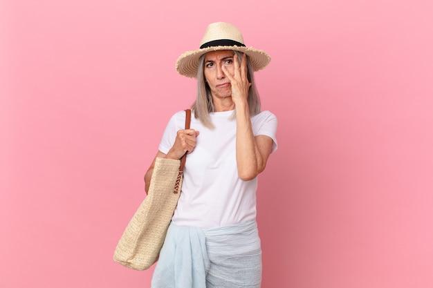 Mulher de meia-idade de cabelo branco se sentindo entediada, frustrada e com sono depois de um cansativo. conceito de verão