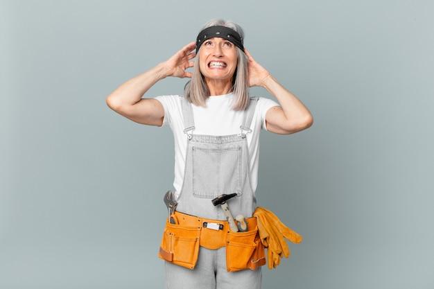Mulher de meia-idade de cabelo branco se sentindo estressada, ansiosa ou com medo, com as mãos na cabeça e usando roupas de trabalho e ferramentas. conceito de limpeza