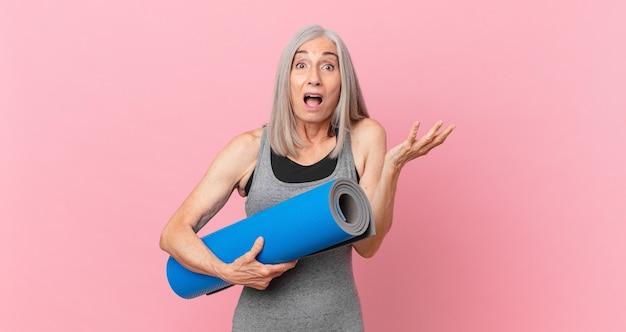 Mulher de meia-idade de cabelo branco se sentindo extremamente chocada e surpresa e segurando um tapete de ioga. conceito de fitness