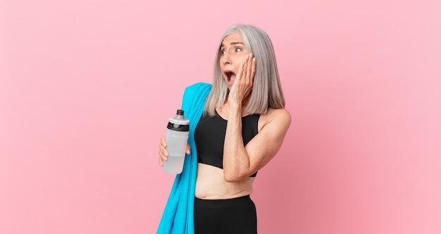 Mulher de meia-idade de cabelo branco se sentindo feliz, animada e surpresa com uma toalha e uma garrafa de água. conceito de fitness