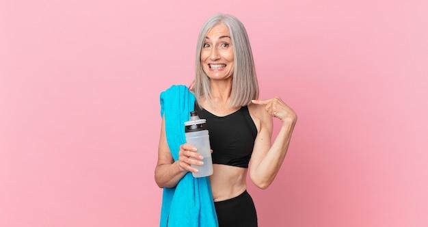 Mulher de meia-idade de cabelo branco se sentindo feliz e apontando para si mesma com um animado com uma toalha e uma garrafa de água. conceito de fitness