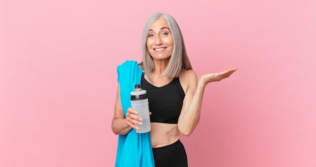 Mulher de meia-idade de cabelo branco se sentindo feliz e surpresa com algo inacreditável com uma toalha e uma garrafa de água. conceito de fitness