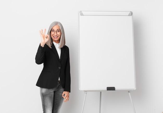 Mulher de meia-idade de cabelo branco se sentindo feliz, mostrando aprovação com um gesto certo e um espaço de cópia da placa. conceito de negócios