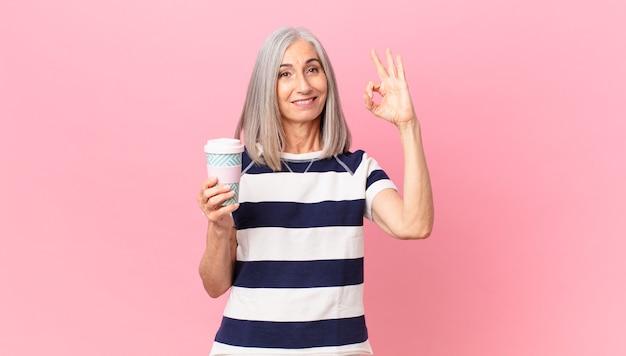 Mulher de meia-idade de cabelo branco se sentindo feliz, mostrando aprovação com um gesto de ok e segurando uma lata de café para viagem