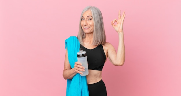 Mulher de meia-idade de cabelo branco se sentindo feliz, mostrando aprovação com um gesto ok com uma toalha e uma garrafa de água. conceito de fitness