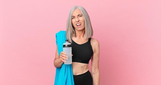 Mulher de meia-idade de cabelo branco se sentindo intrigada e confusa com uma toalha e uma garrafa de água. conceito de fitness