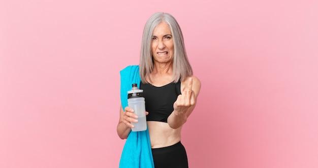 Mulher de meia-idade de cabelo branco se sentindo irritada, irritada, rebelde e agressiva com uma toalha e uma garrafa de água. conceito de fitness