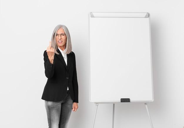 Mulher de meia-idade de cabelo branco se sentindo irritada, irritada, rebelde e agressiva e um espaço de cópia da placa. conceito de negócios