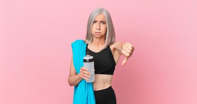 Mulher de meia-idade de cabelo branco se sentindo mal, mostrando os polegares para baixo com uma toalha e uma garrafa de água. conceito de fitness