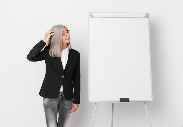 Mulher de meia-idade de cabelo branco se sentindo perplexa e confusa, coçando a cabeça e um espaço de cópia da placa. conceito de negócios