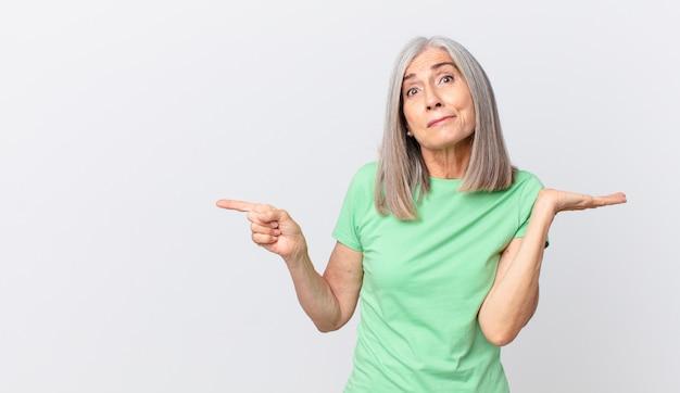 Mulher de meia-idade de cabelo branco se sentindo perplexa e confusa, duvidando e apontando para o lado