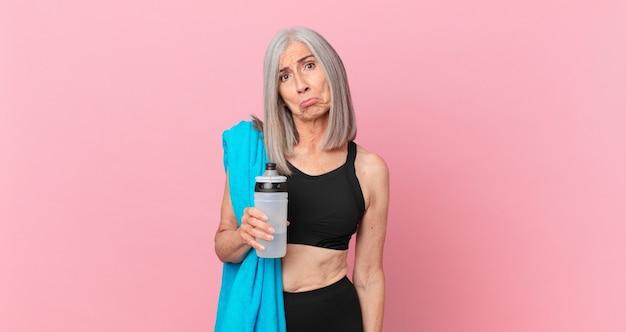 Mulher de meia-idade de cabelo branco se sentindo triste e resmungona com um olhar infeliz e chorando com uma toalha e uma garrafa de água. conceito de fitness