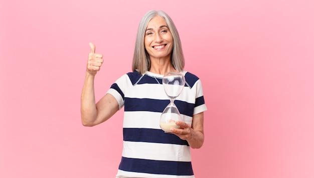 Mulher de meia-idade de cabelo branco segurando um cronômetro de ampulheta