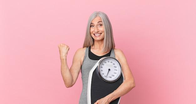 Mulher de meia-idade de cabelo branco segurando uma balança. conceito de fitness e dieta