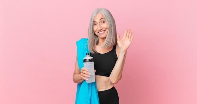 Mulher de meia-idade de cabelo branco sorrindo alegremente, acenando com a mão, dando as boas-vindas e cumprimentando você com uma toalha e uma garrafa de água. conceito de fitness