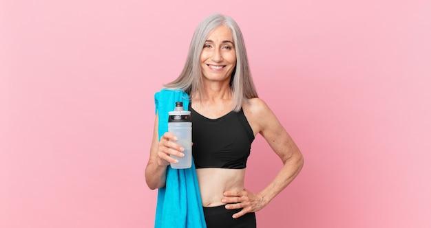 Mulher de meia-idade de cabelo branco sorrindo alegremente com uma mão no quadril e confiante com uma toalha e uma garrafa de água. conceito de fitness