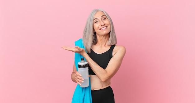 Mulher de meia-idade de cabelo branco sorrindo alegremente, sentindo-se feliz e mostrando um conceito com uma toalha e uma garrafa de água. conceito de fitness