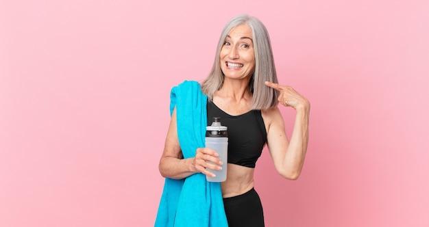 Mulher de meia-idade de cabelo branco sorrindo com confiança, apontando para o próprio sorriso largo com uma toalha e uma garrafa de água. conceito de fitness