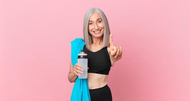 Mulher de meia-idade de cabelo branco sorrindo com orgulho e confiança fazendo o número um com uma toalha e uma garrafa de água. conceito de fitness
