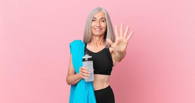 Mulher de meia-idade de cabelo branco sorrindo e parecendo amigável, mostrando o número cinco com uma toalha e uma garrafa de água. conceito de fitness
