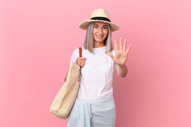 Mulher de meia-idade de cabelo branco sorrindo e parecendo amigável, mostrando o número cinco. conceito de verão