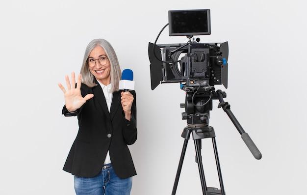 Mulher de meia-idade de cabelo branco sorrindo e parecendo amigável, mostrando o número cinco e segurando um microfone. conceito de apresentador de televisão