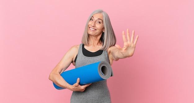 Mulher de meia-idade de cabelo branco sorrindo e parecendo amigável, mostrando o número cinco e segurando um tapete de ioga. conceito de fitness