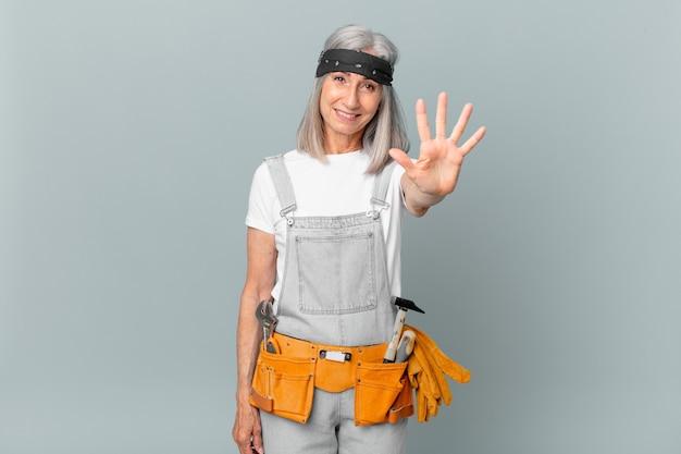 Mulher de meia-idade de cabelo branco sorrindo e parecendo amigável, mostrando o número cinco e usando roupas de trabalho e ferramentas. conceito de limpeza