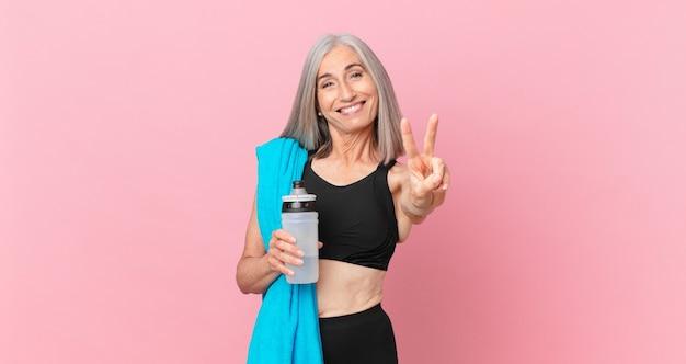 Mulher de meia-idade de cabelo branco sorrindo e parecendo amigável, mostrando o número dois com uma toalha e uma garrafa de água. conceito de fitness
