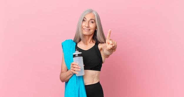 Mulher de meia-idade de cabelo branco sorrindo e parecendo amigável, mostrando o número um com uma toalha e uma garrafa de água. conceito de fitness